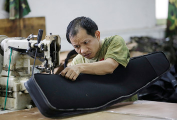 A worker sews a gun case on the production line of a factory of firearm equipment manufacturer Yakeda Tactical Gear Co, which exports most of its products to the United States, in Guangzhou