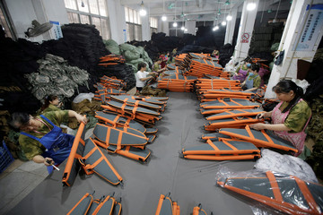 Women work on rifle cases for a client on the production line in a factory of firearm equipment manufacturer Yakeda Tactical Gear Co, which exports most of its products to the United States, in Guangzhou