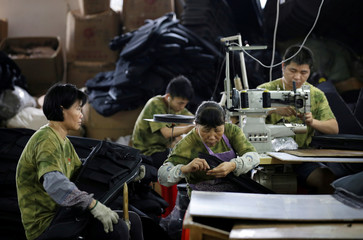 Workers sew gun cases for a lient on the production line of a factory of firearm equipment manufacturer Yakeda Tactical Gear Co, which exports most of its products to the United States, in Guangzhou