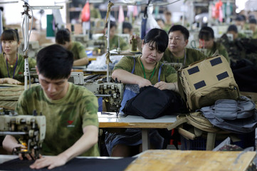People work on the production line at a factory of firearm equipment manufacturer Yakeda Tactical Gear Co, which exports most of its products to the United States, in Guangzhou