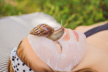 Young woman makes a face mask with snail mucus. Snail crawling on a face mask