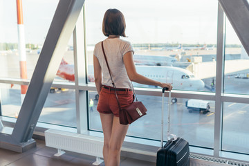 Young woman traveler in airport near gate windows at planes on runway.