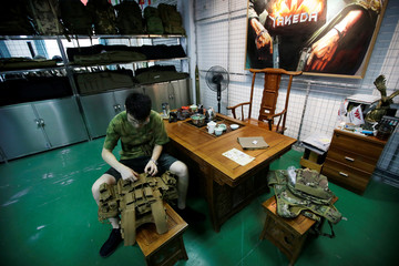 A manager checks a tactical vest at an office of a factory of firearm equipment manufacturer Yakeda Tactical Gear Co, which exports most of its products to the United States, in Guangzhou