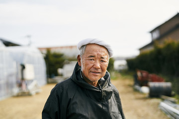 Portrait of senior farmer standing outdoors
