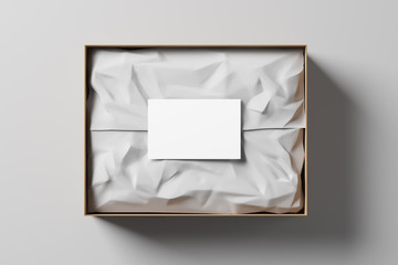 Open gift box with white wrapping paper and business card on a light background. Business gift. Mock up. Top view. 3d rendering