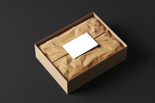 Realistic open cardboard box with white wrapping paper and a business card on a black background. Side view. Mock up. 3d rendering