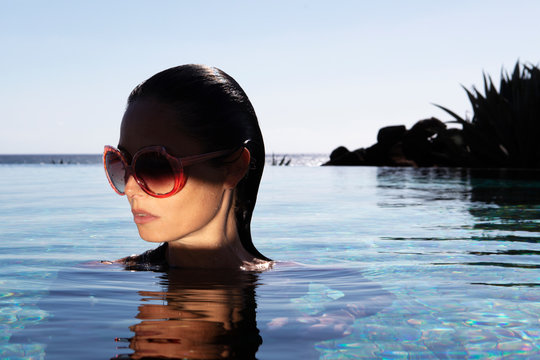 Jeune femme lunette, piscine au soleil