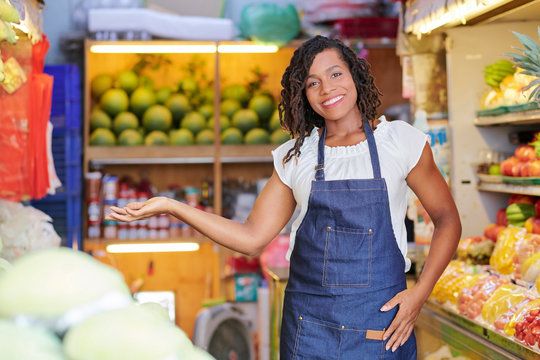 Smiling pretty saleswoman inviting you to supermarket with fresh organic fruits and vegetables