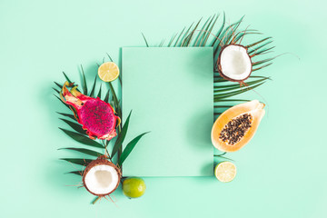Summer composition. Tropical palm leaves, fruits, paper blank on mint green background. Summer concept. Flat lay, top view, copy space