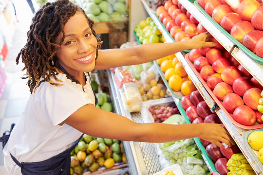 Pretty smiling Black woman working at fruit department at grocery store