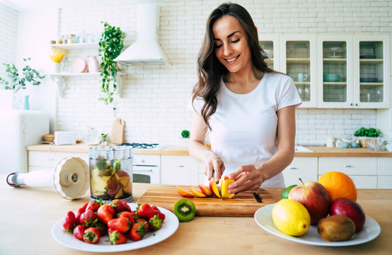 Beautiful woman making fruits smoothies with blender. Healthy eating lifestyle concept portrait of beautiful young woman preparing drink with bananas, strawberry and kiwi at home in kitchen.