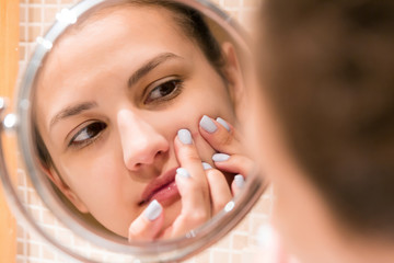 Young girl squeezes pimple on the fer face in front of a bathroom mirror. Beauty skincare and wellness morning concept