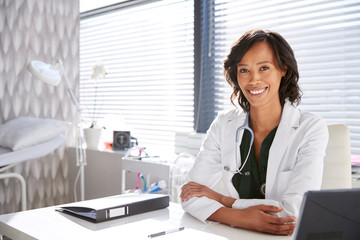 Portrait Of Smiling Female Doctor Wearing White Coat With Stethoscope Sitting Behind Desk In Office