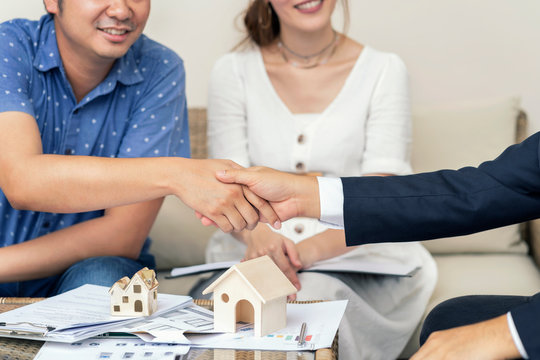 Close up, Man shaking hands represent sale, Asian couple meeting financial adviser for home, real estate purchase, success business contract deals with sale. Success deals.