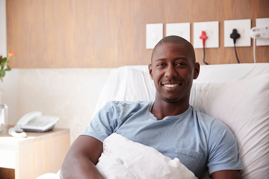 Portrait Of Male Patient Lying In Hospital Bed Smiling At Camera