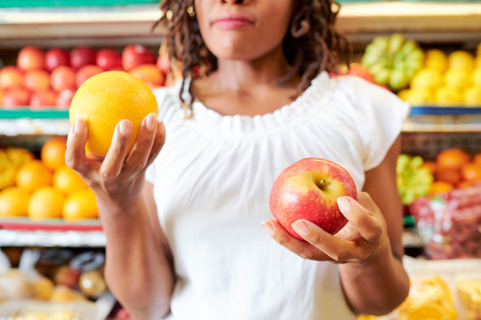 Young woman choosing between apple and orange when shopping at supermarket