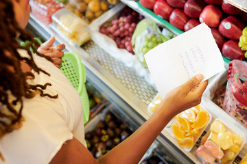 Female customer following shopping list when buying fruits and berries at supermarket