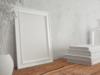 Empty frame on wooden table with books and plant. Concrete wall. Rendering made using free software Blender