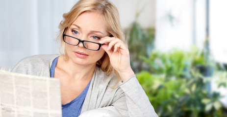 news, press, mass media and people concept - woman in eyeglasses reading newspaper at home