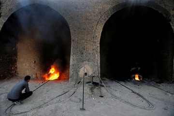 An Iraqi worker checks a chimney stack outlets at the brick factory in the town of Nahrawan in Baghdad