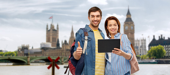 travel, tourism and vacation concept - happy couple of tourists with tablet computer and backpacks showing thumbs up over london city background