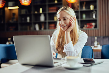Beautiful smiling Caucasian blonde female blogger dressed smart casual sitting in cafeteria and using laptop.