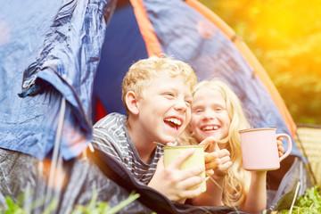 Zwei Kinder zelten zusammen im Sommer