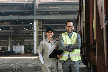 Portrait of metal industry manager and female technician smiling at camera in large warehouse.