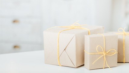 Delivery service. Rustic paper handmade gift boxes on white table over defocused white background. Copy space.