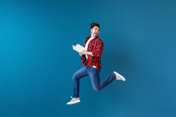 Jumping young man with book on color background