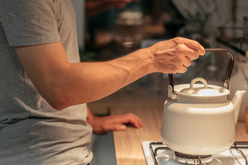 Night habit and insomnia. Tea preparation. Cropped shot of man putting old style kettle on stove. Wall mural