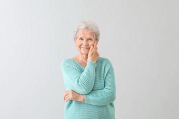 Portrait of senior woman on light background Fototapete