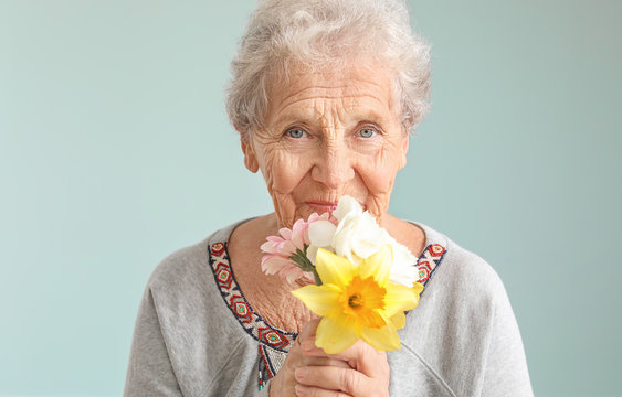 Portrait of senior woman with bouquet of flowers on grey background