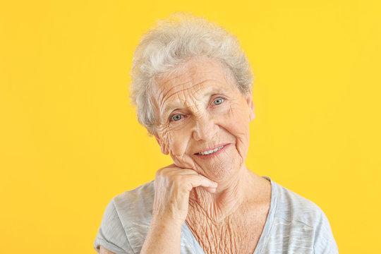 Portrait of senior woman on color background