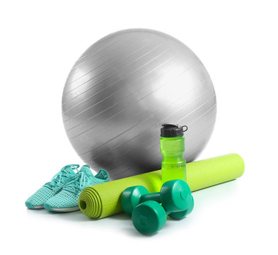 Set of sports equipment with fitness ball, shoes and bottle of water on white background