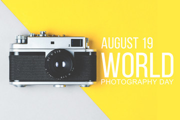 Old retro photo camera on grey-yellow background. World photography day poster