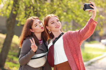 Beautiful young women taking selfie in park