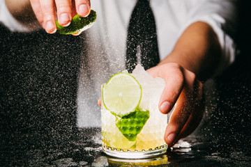 Close-up of professional bartender squeezing lime making Caipirinha cocktail