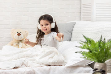 little child baby girl listening to the music with the headphones on bed. happy morning