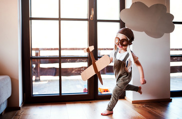 Fototapeta A toddler boy with carton plane playing indoors at home, flying concept.