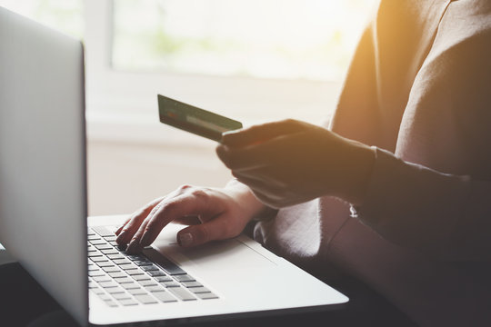 young man using laptop and holding credit card, online shopping concept