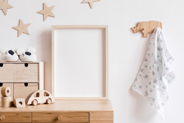 Stylish scandi childroom withwooden mock up photo frame, wooden toys, boxes, blocks and accessories Stars pattern on the background wall. Bright and sunny interior with wooden desk. Home decor.