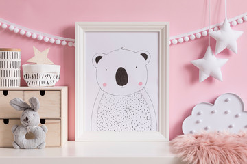 Modern scandinavian newborn baby room with mock up poster frame, plush rabbit, wooden box, cloud and children accessories. Cozy interior with pink walls. Haniging cotton garland and stars. Template