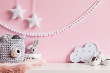 Cozy scandinavian newborn baby room with gray basket ,white stars lamp, cloud, plush rabbit and children accessories. Stylish interior with pink walls and haniging white garland.Template. Copy space.