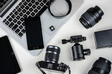 Material y herramientas de trabajo de fotografía y edición de imágenes formado por teléfono móvil, ordenador, cámara mirrorless, tablet, objetivos reflex, nivel, flash, y rótula.