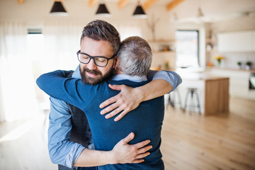 An adult son and senior father indoors at home, hugging.