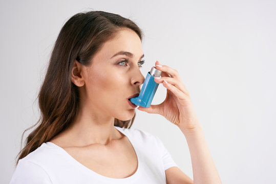 Asthmatic woman using an asthma inhaler during asthma attacks