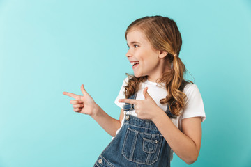 Pretty young little girl posing isolated over blue wall background pointing. Wall mural