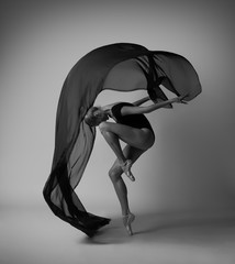 Girl with flying black cloth. Black and white photo.