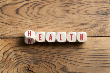 """cubes showing the word """"health"""" and """"wealth"""" at the same time, symbolizing to keep the balance"""